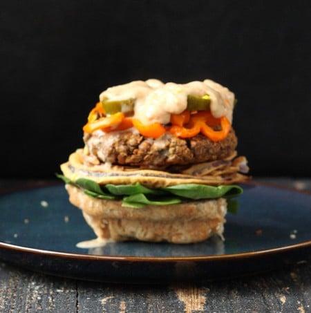 loaded vegan lentil burger without the bun top on a blue plate