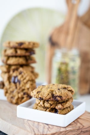 pistachio cookies on white plate with stack of vegan cookies in bakground on wooden board