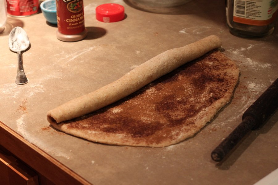 cinnamon filled dough rectangle being rolled into a roll to make vegan cinnabons