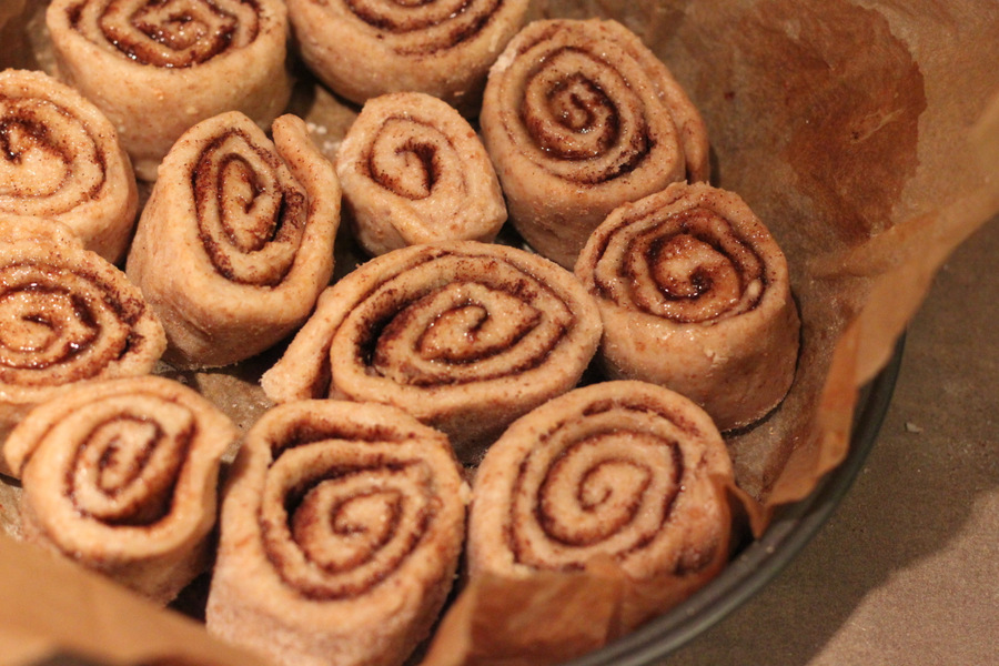 vegan cinnamon rolls proofing in a round parchment-lined cake pan
