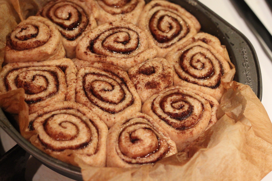 risen vegan cinnamon buns in a round cake pan ready to be baked