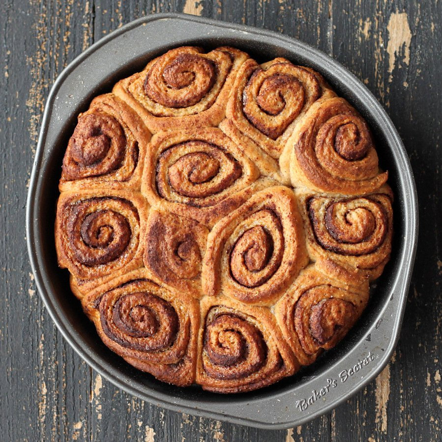 overhead shot of freshly baked Vegan Cinnamon rolls in a round metal cake pan