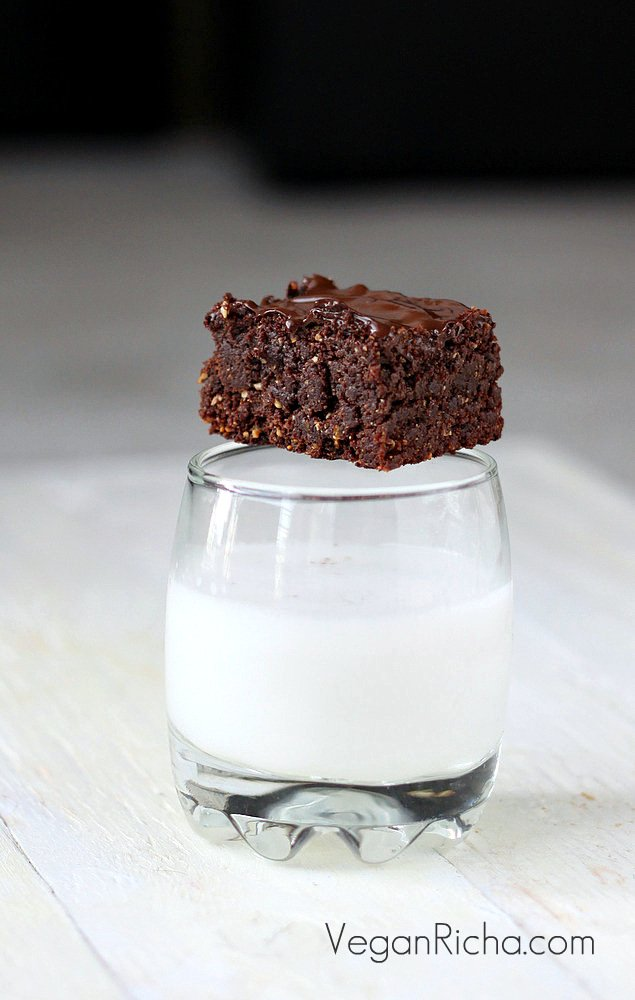 a vegan triple chocolate salted caramel brownie placed on a milk glass