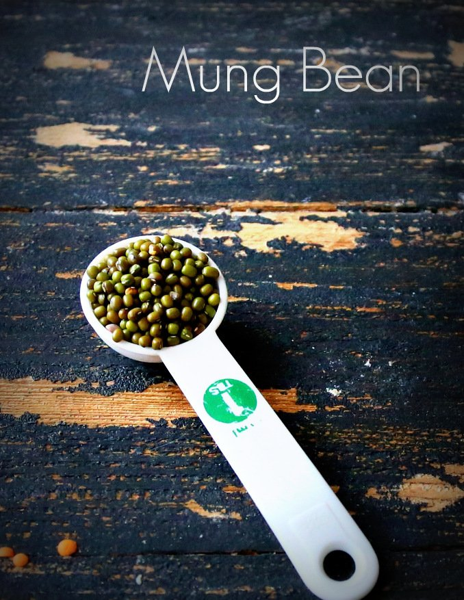 a white plastic teaspoon with mung beans on a black wooden table