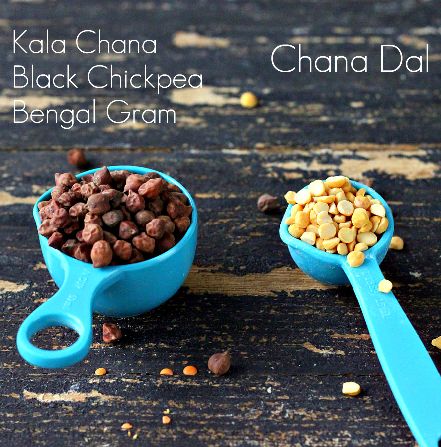a small blue plastic measuring cup with black chickpeas next to a teaspoon with split peas