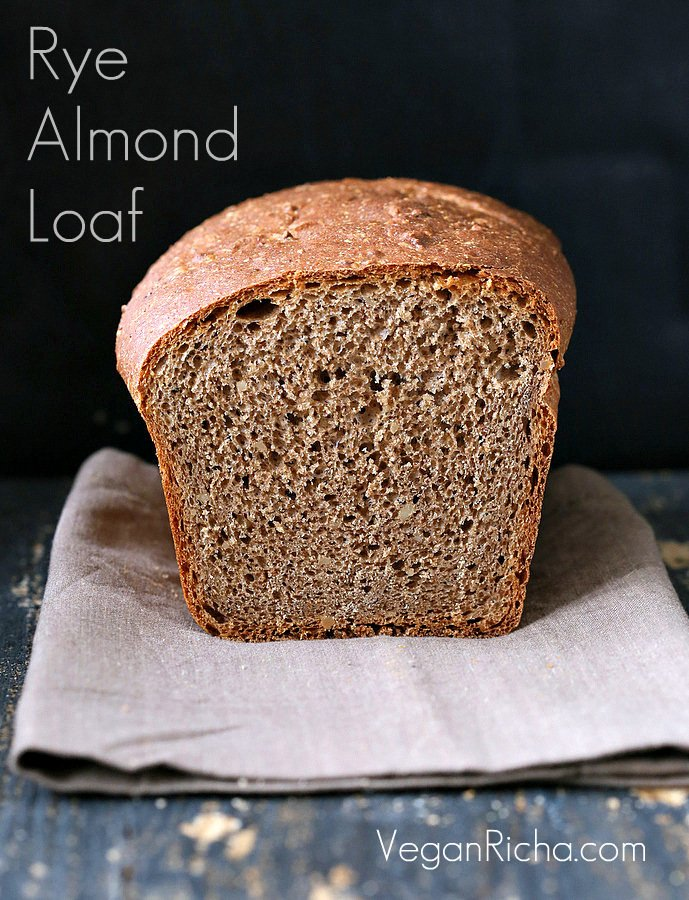 a sliced-open loaf of whole wheat rye and almond flour sandwich bread on a light brown kitchen towel