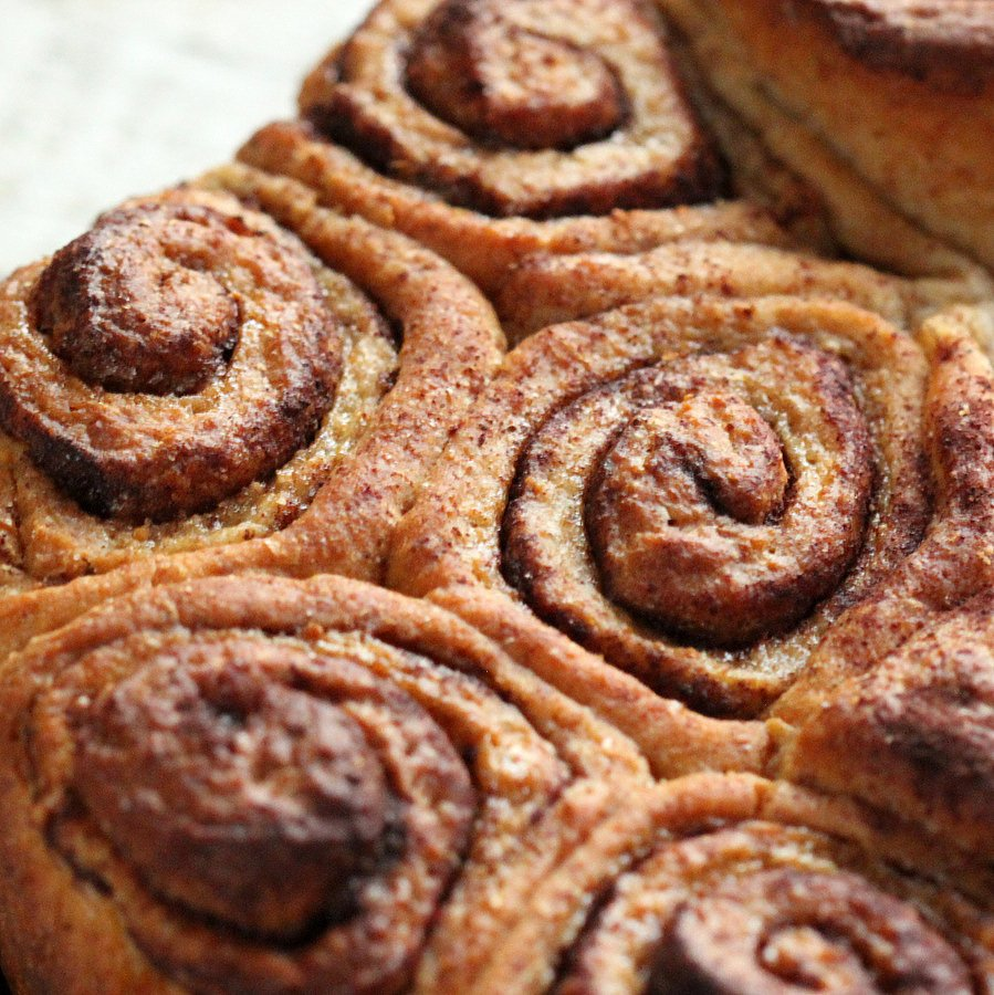 close-up of freshly baked vegan cinnamon rolls in a round cake pan