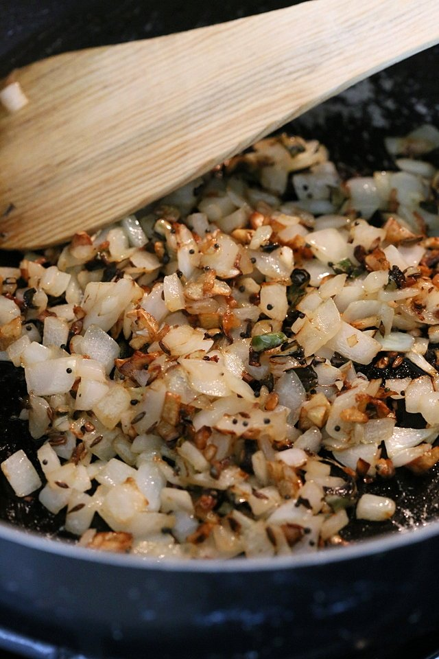 Onion and garlic getting cooked in a skillet for ourVegan Dal Makhani Recipe #veganricha #vegandalmakhani #instanpotdalmakhani