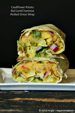 a stacked red lentil hummus wrap against a black background