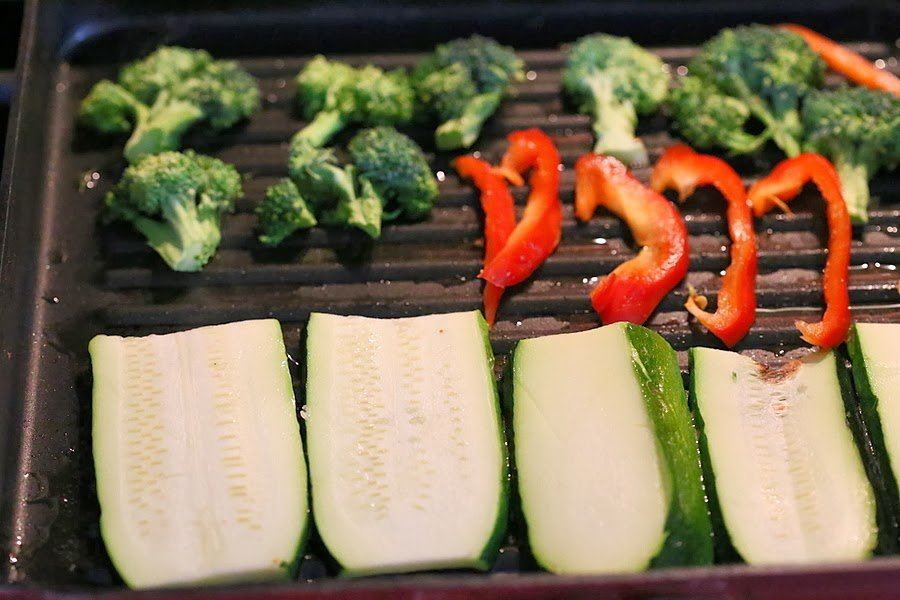 sliced zucchini, red bell peppers and broccoli florets in a grill pan