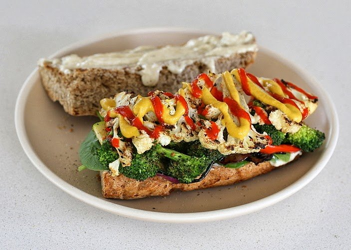open-faced vegan grilled vegetable sandwich with plenty of sriracha mayo and mustard drizzled on top