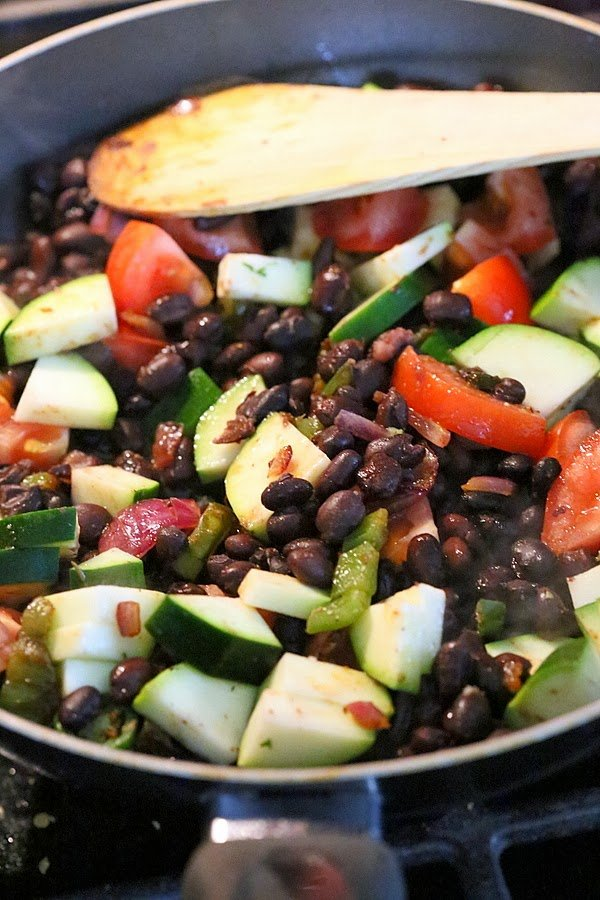 vegetarian filling for a vegan wrap recipe being sauteed in a black pan