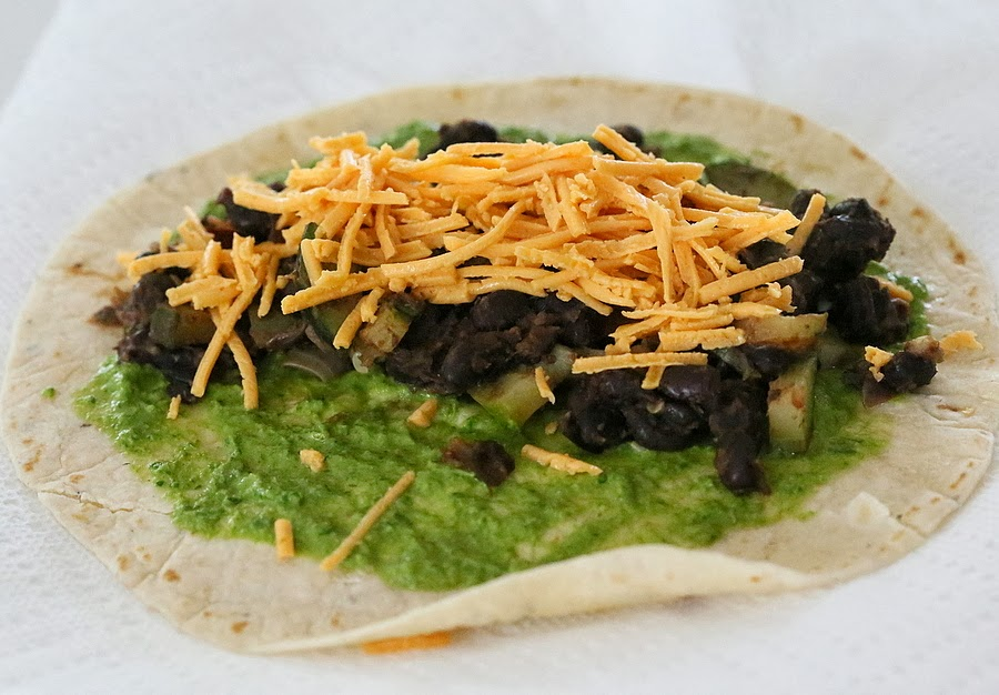 a wheat wrap being topped with chimichurri, black beans and vegan shredded cheese