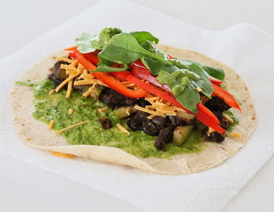 a wheat tortilla wrap topped with black beans, spinach and dairy-free cheese