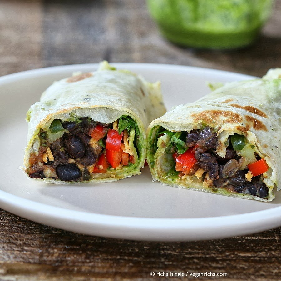 a halved healthy vegan wrap with smoky black beans, spinach, chimichurri and vegan cheese on a white plate