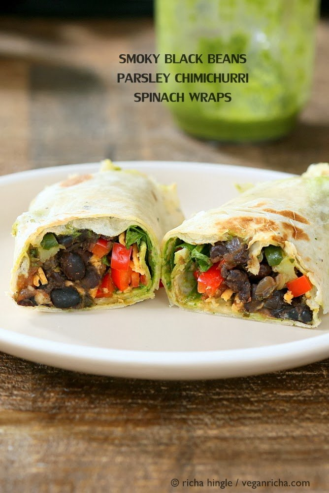 side view of two halves of a vegan wrap with black beans, bell pepper and vegan cheese on a white plate