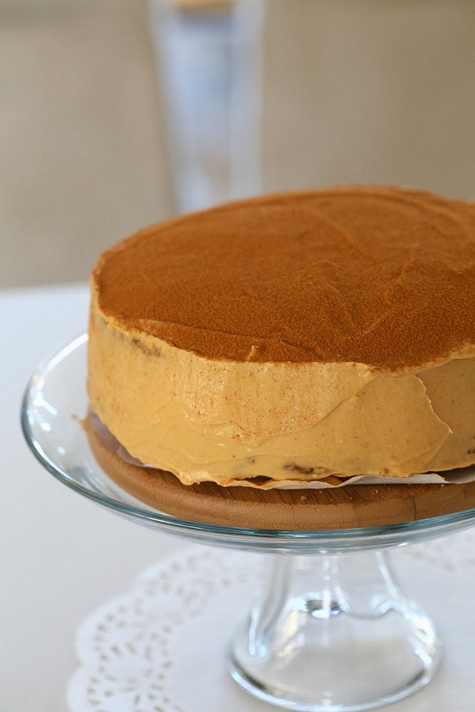 side view of a vegan pumpkin mousse cake on a glass cake stand