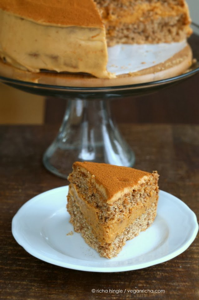 a slice of vegan pumpkin mousse cake with spelt flour vanilla sponge on a white dessert plate