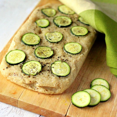 A loaf of Gluten-free Zucchini Basil Focaccia on a cutting board with slices of zucchini next to it