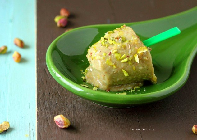 A pistachio kulfi icecream popsicle on a green plate