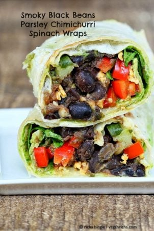 a healthy vegan wrap cut in half revealing a black bean and spinach filling