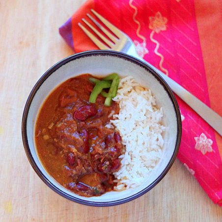 A bowl of red kidney bean curry and rice with a fork and red napkin