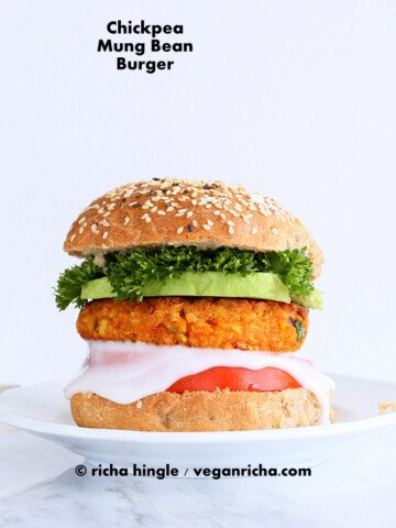 Spicy Chickpea Burger with toppings on sesame seed bun on a white plate