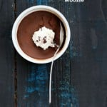 Vegan Chocolate Mousse in a white ramekin with coconut whipped cream and a spoon