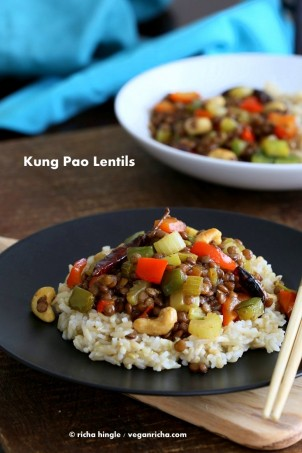 Kung Pao Lentils over brown rice on a black plate with chopsticks