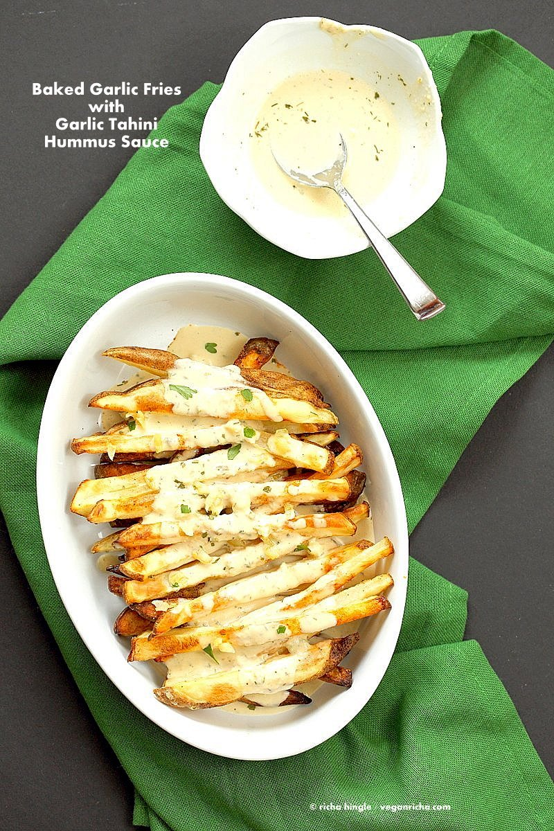 Baked Fries with Garlic Sauce - Russet potato baked and drenched in garlic tahini hummus lemon sauce and golden garlic | VeganRicha.com #vegan #appetizer #glutenfree #soyfree #recipe