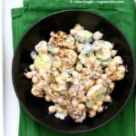 Vegan potato salad in a black bowl on a green kitchen towel