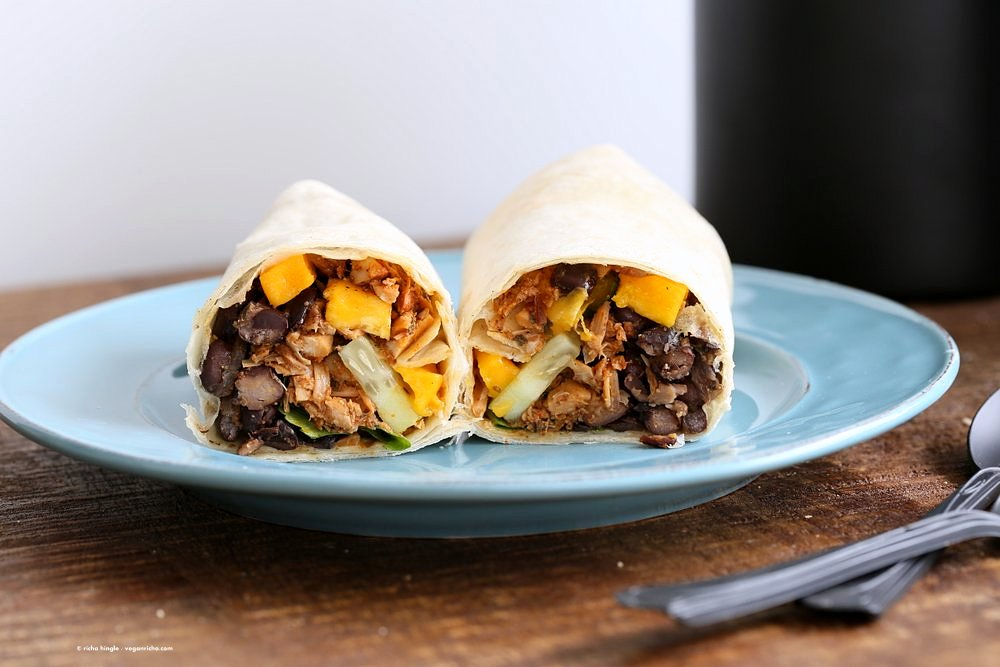 Jamaican Jerk Jackfruit Caribbean Black Bean Mango Wraps. These Burritos are packed with hot shredded jerk jackfruit, black beans, mango and cucumbers. Serve as wraps or make a sandwich or bowl. Vegan Soy-free Recipe. Can be gluten-free | VeganRicha.com