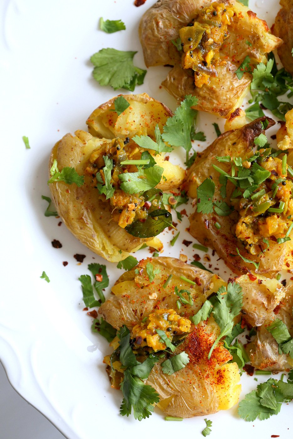 Indian Spiced Smashed Potatoes with Mustard Ginger Tempering. Bonda like Samosa is a spiced potato snack. These smashed potatoes are topped with Bonda style tempering of ginger, chile, turmeric and mustard seeds. Vegan Gluten-free Recipe   VeganRicha.com