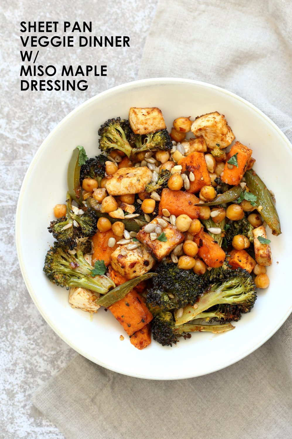 Sheet Pan Veggie Dinner with Roasted Veggies, Chickpeas, Tofu in a white Bowl over grey napkin and concrete
