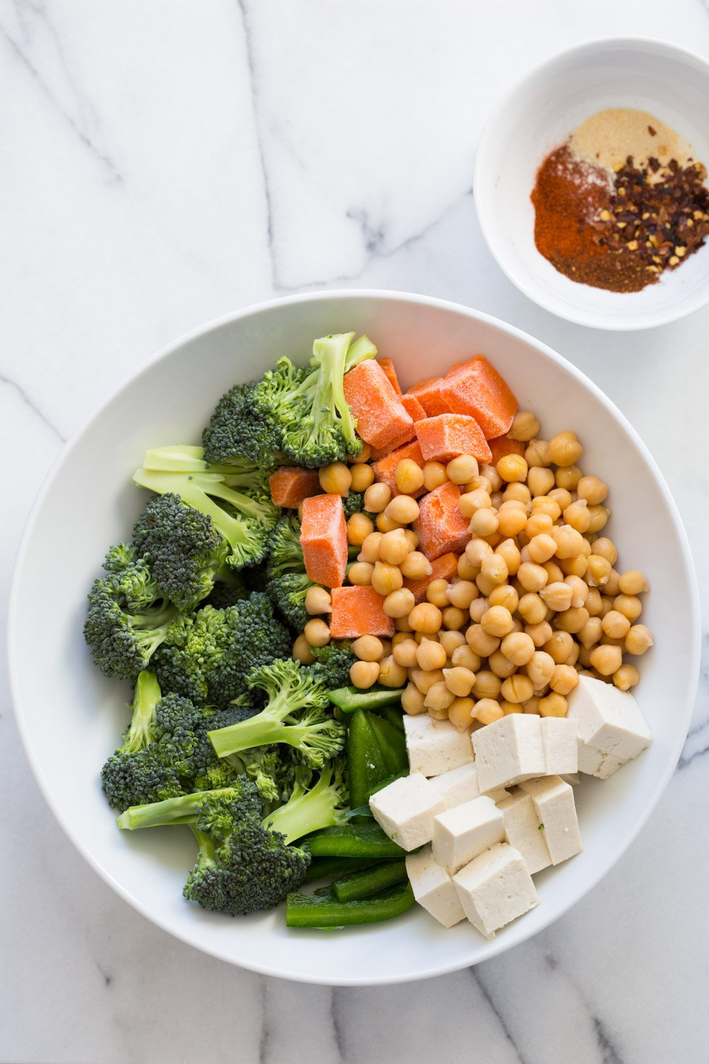 Chickpeas, Tofu, Broccoli, Sweet Potato in a White Bowl with spice bowl on the side
