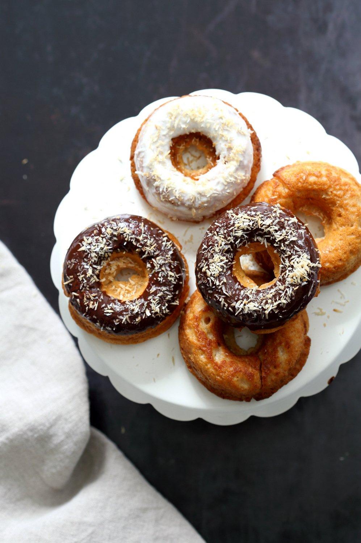 Vegan Banana Donuts with vanilla and chocolate icing on white cake stand