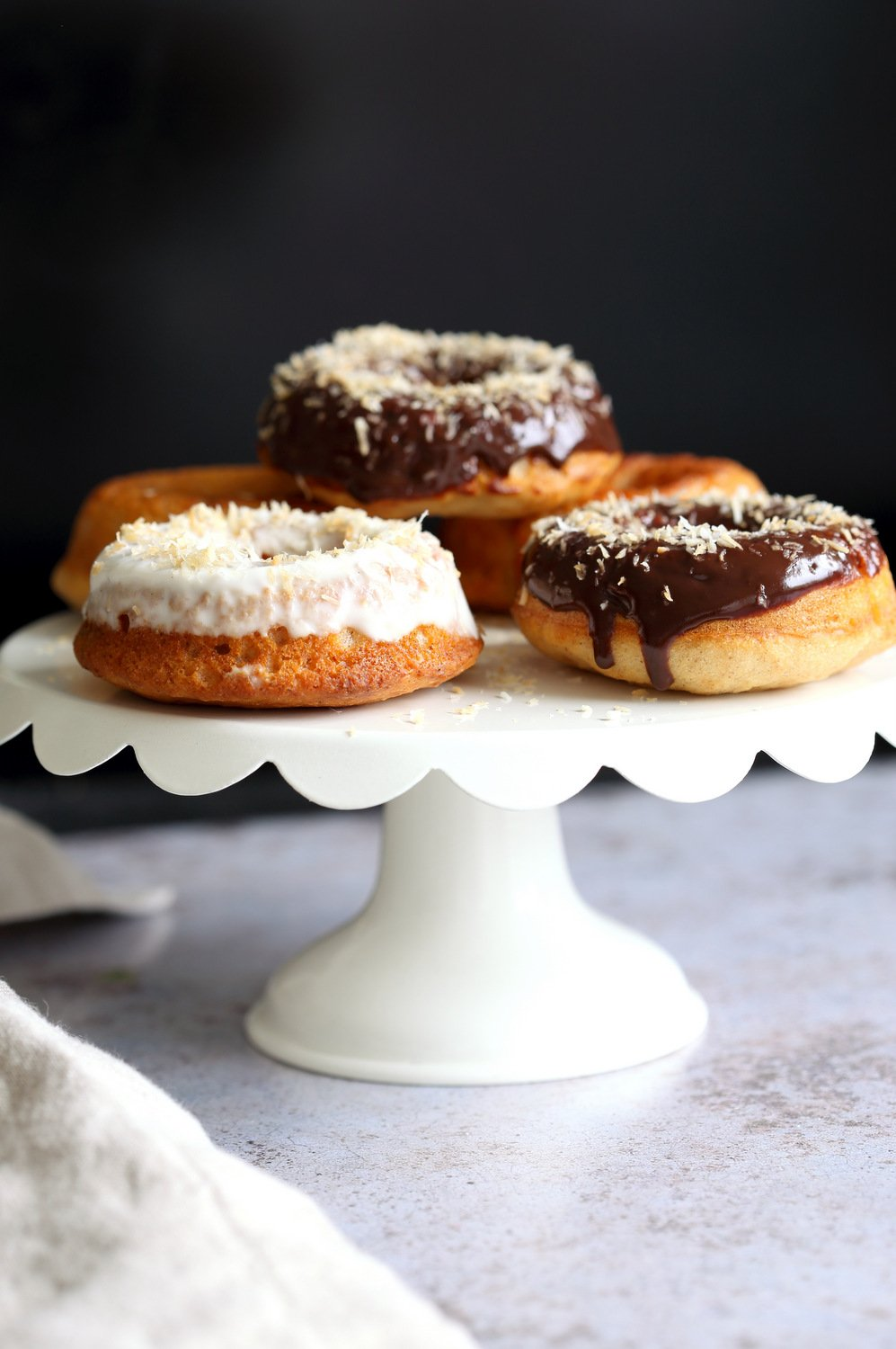 Vegan Banana Donuts with vanilla and chocolate icing on white cake stand