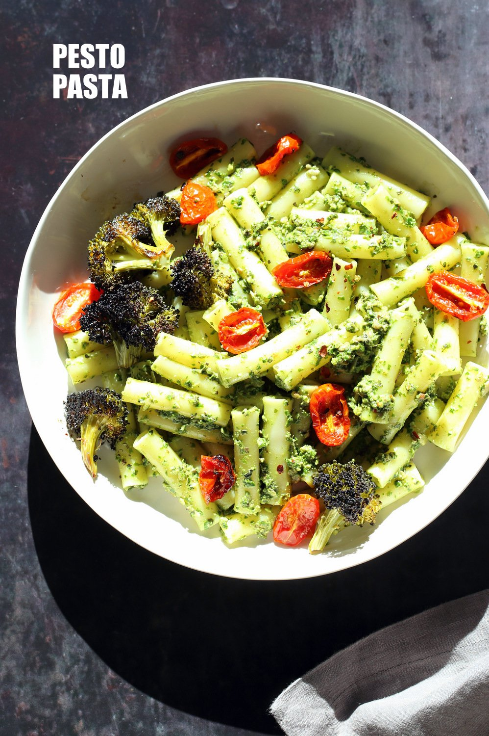 Large While Bowl with Vegan Pesto Pasta with Ziti, roasted cherry tomatoes and Charred broccoli on black stone