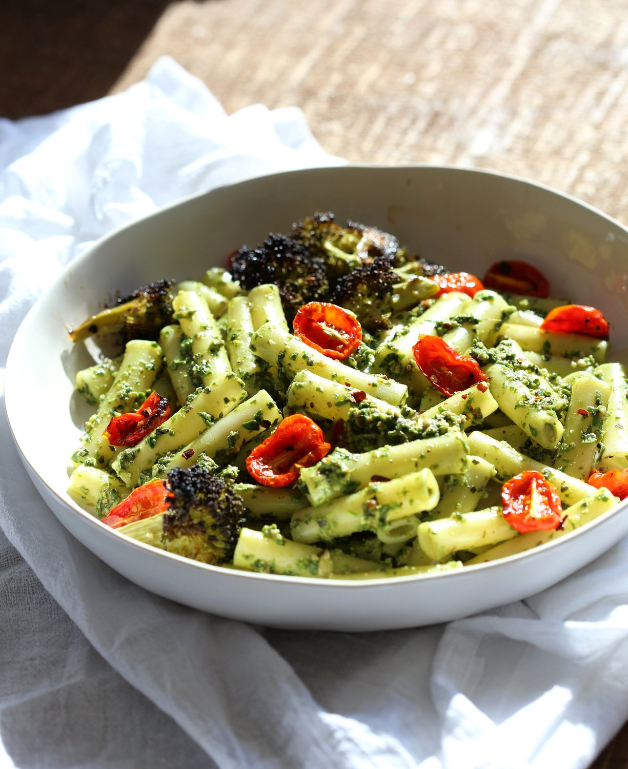Large While Bowl with Vegan Pesto Pasta with Ziti, roasted cherry tomatoes and Charred broccoli on wood table
