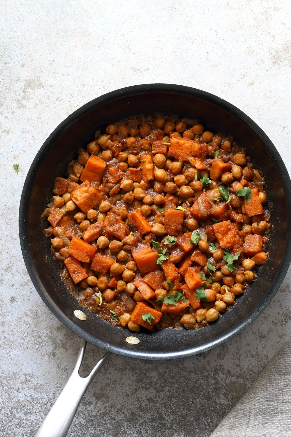 Our Harrisa Chickpea Stew in Black Skillet over Concrete