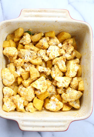 Our Vegan Baked Aloo Gobi Spiced Potatoes and Cauliflower ingredients mixed and ready to bake in a baking dish