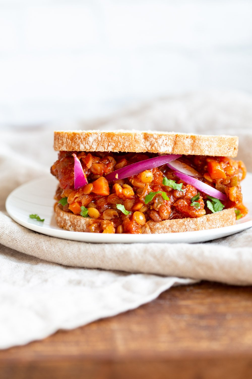 Our Vegan Lentil Sloppy joes serves in a sandwich with onions