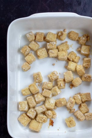 Baked Tofu cubes in a white baking dish for our Orange Tofu Recipe