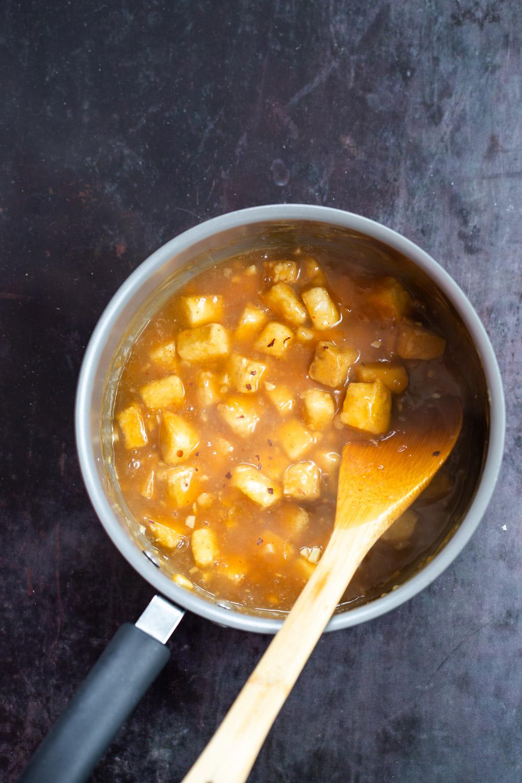 Baked Tofu Mixed with Orange Sauce in a saucepan our Orange Tofu Recipe