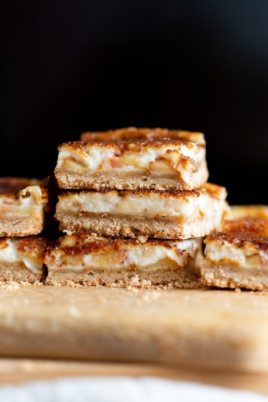 Sliced Vegan Apple Custard Squares stacked on wood board