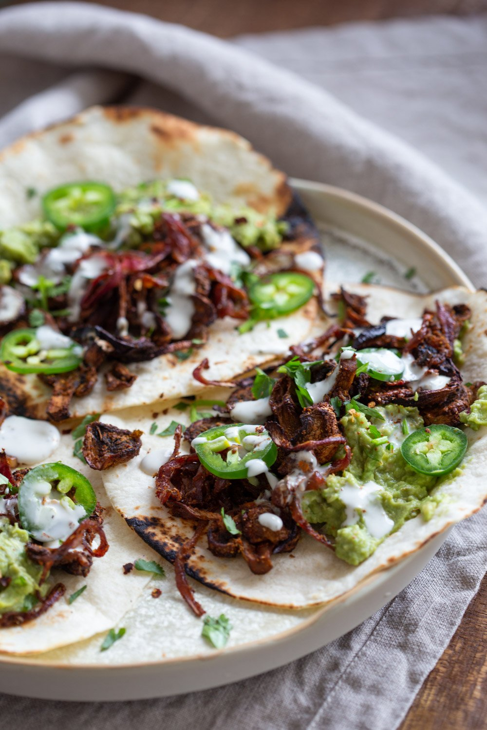 Vegan Carnitas. Mushrooms marinated in Spicy Smoky Zesty Marinade, Baked and served with toppings in tacos, wraps, burritos. Use jackfruit for variation. #vegan #Glutenfree #Nutfree #Recipe. Soyfree option #VeganRicha #mushroomcarnitas #veganarnitas