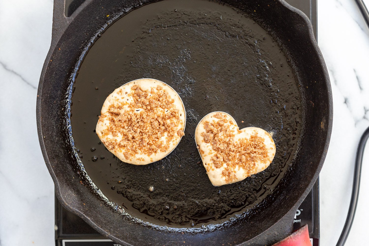 Vegan Cinnamon Streusel Pancakes getting cooked on a cast iron skillet