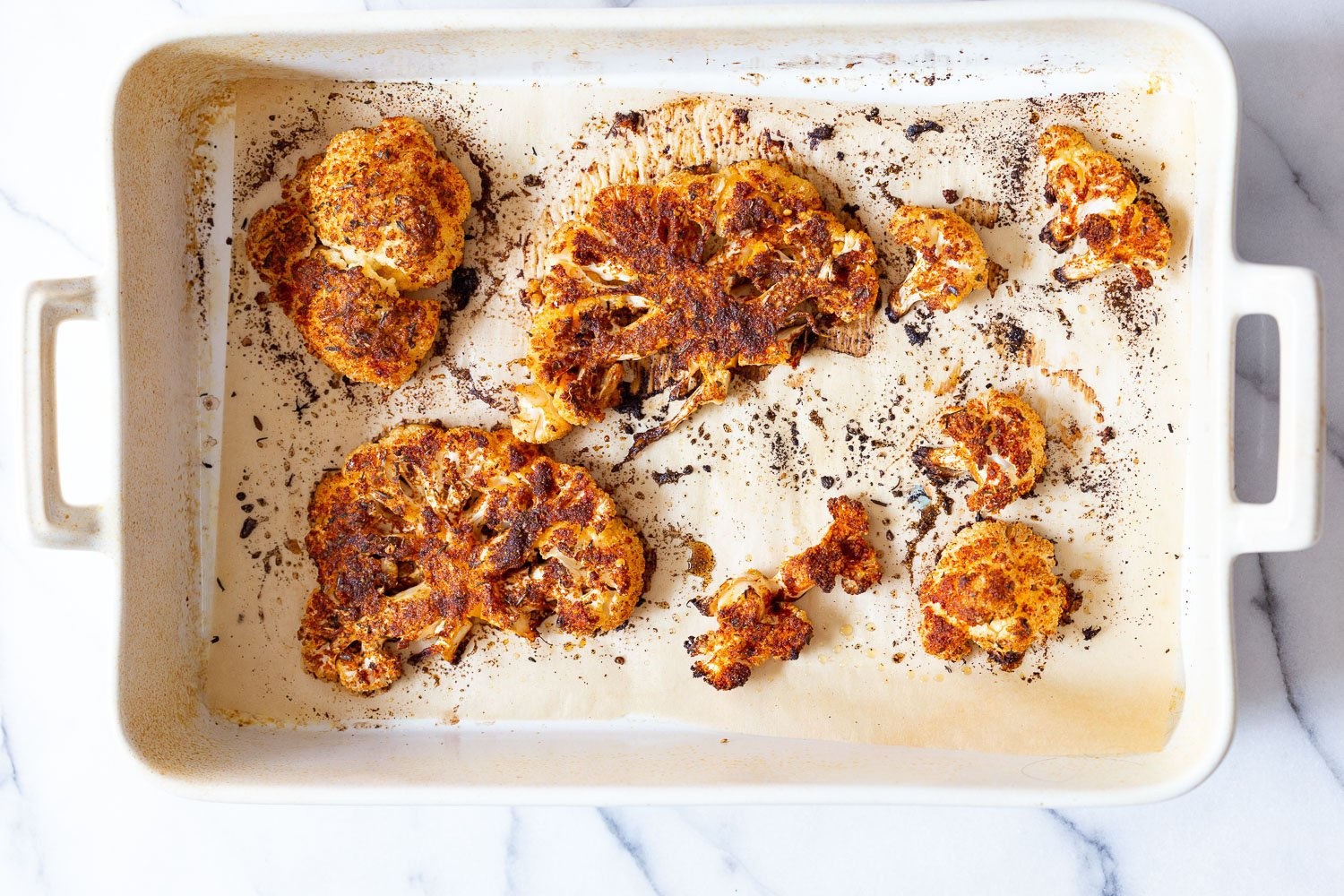 Baked Cajun Roasted Cauliflower Steaks Slices on parchment line white baking dish