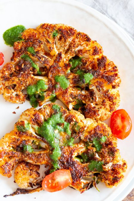 "Vegan Cajun Roasted Cauliflower ""Steaks"" with Chimichurri Sauce. Slice into thick slices or just chop into florets to make this delicious Cajun Cauliflower. Serve with chimichurri or a cooling dressing. #Vegan #Glutenfree #Soyfree #Nutfree #Recipe #veganRicha #cajunCauliflower"