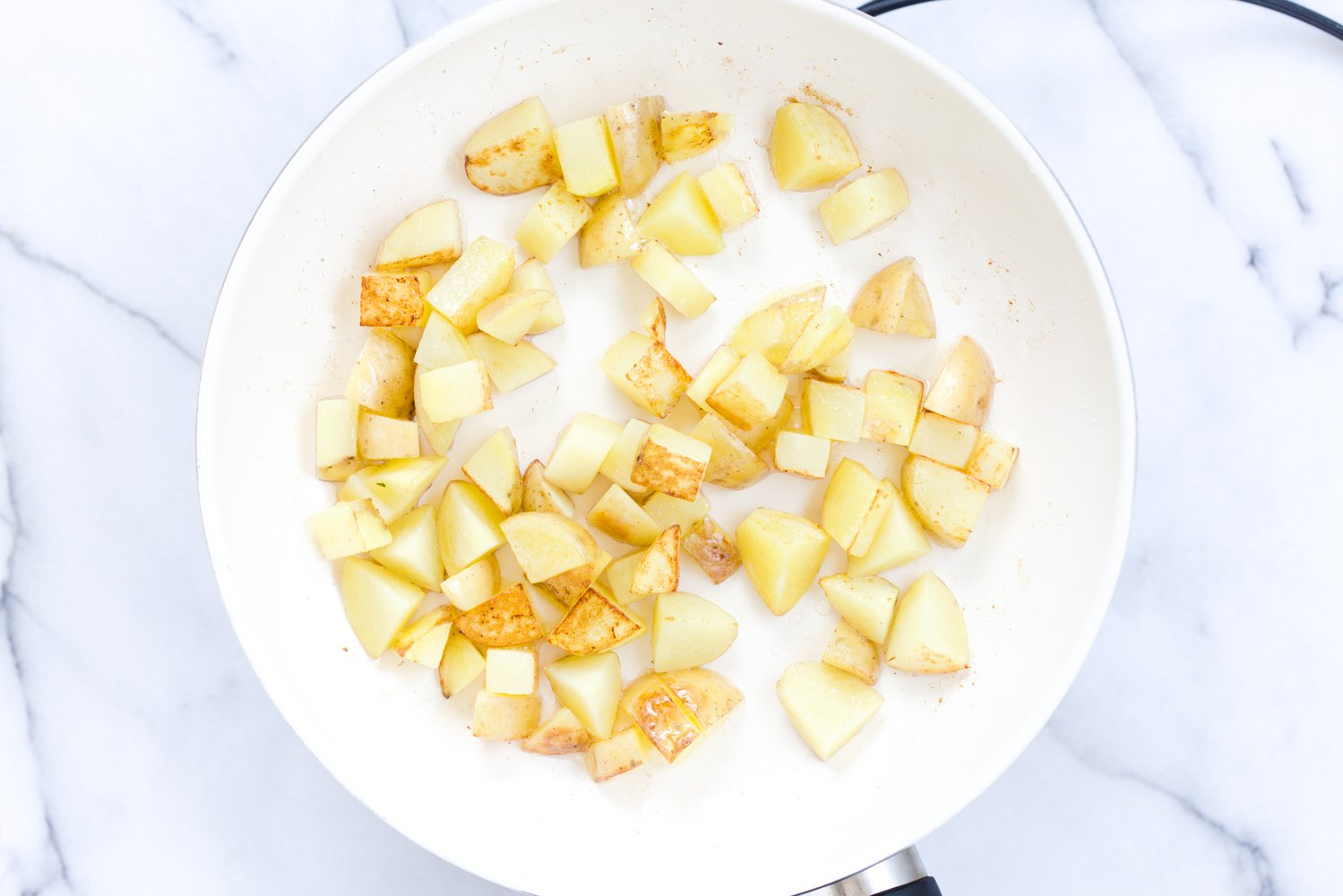 overhead shot of sauteed potato cubes in a white bowl